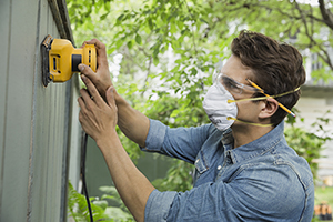 Woman wearing a mask and goggles, holding a power sander.